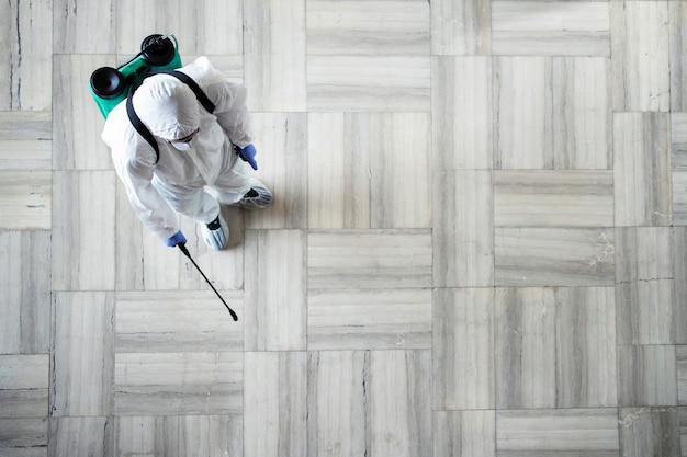 伝染性の高いコロナウイルスの噴霧を停止するために公共エリアの消毒を行う白い化学防護服を着た人 無料写真