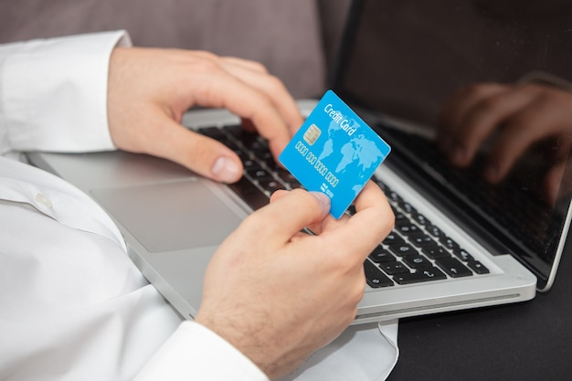 Person inputting details of its credit card in the laptop Free Photo