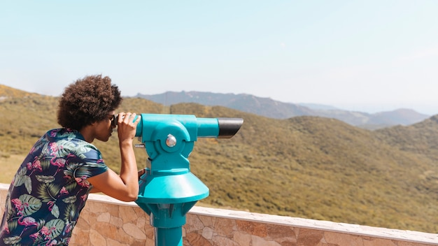 Person looking at landscape through spyglass Free Photo