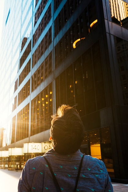Person looking at top of skyscraper Free Photo