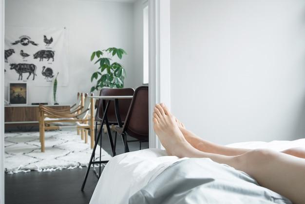 Persona sdraiata sul letto e rilassarsi durante il giorno Foto Gratuite
