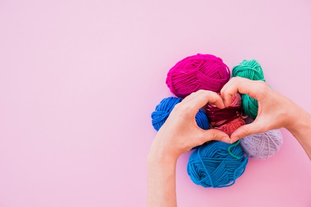 A person making heart over the colorful wool balls on pink background Free Photo