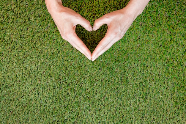 Person making a heart with his hands on grass with copy space Free Photo