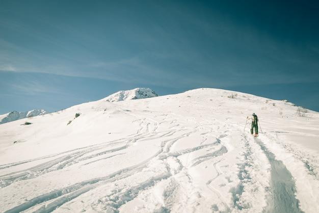 Person mountaineering snowy peak Premium Photo