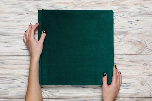 Открытая фотокнига. женщина держит семейный зеленый фотоальбом. женщины держат свадебный фотоальбом Premium Фотографии