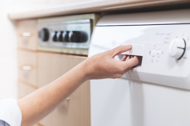 Person opening the dishwasher in the kitchen of the apartment Premium Photo