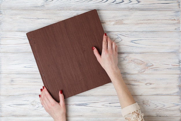 A person opens a photobook. the womans hand holding a family photo album on the table. Premium Photo