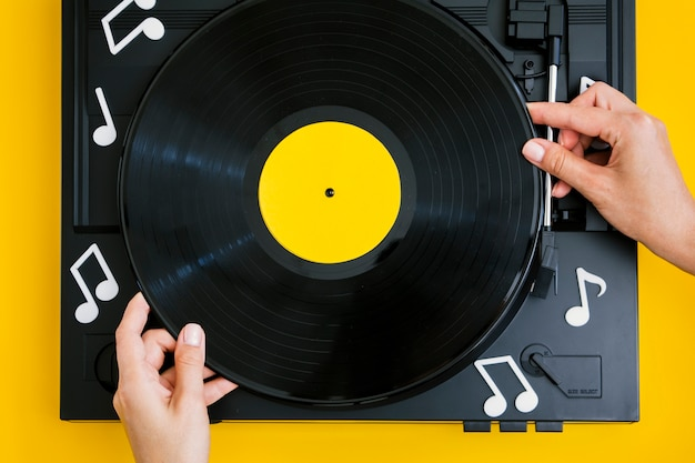 Person placing vinyl record in player Free Photo