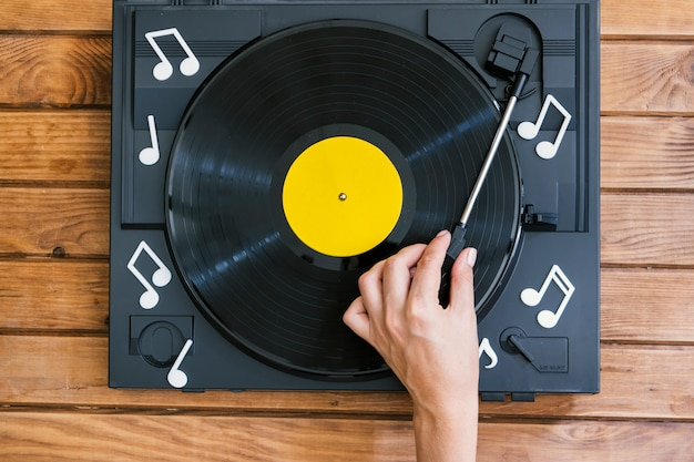 Person playing vinyl record in player Free Photo