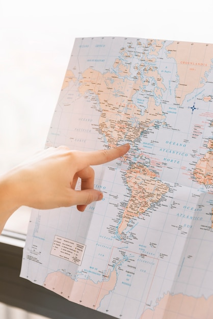 A person pointing finger toward the location on map Free Photo