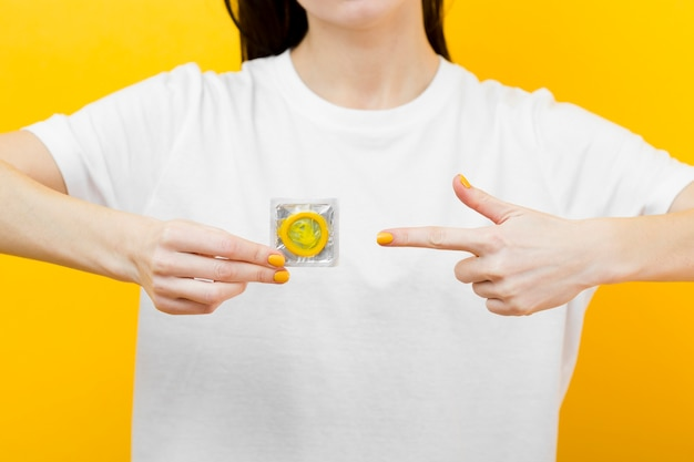 Person pointing to a yellow condom Free Photo