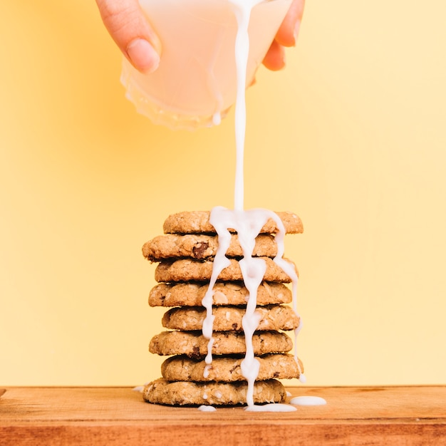 Person pouring milk from glass on cookies stack Free Photo