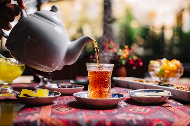 Person pouring tea in armudy jam lemon side view Free Photo