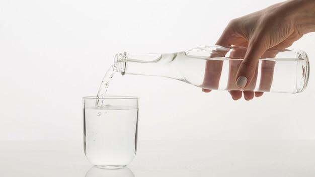 Persona che versa acqua in vetro Foto Gratuite