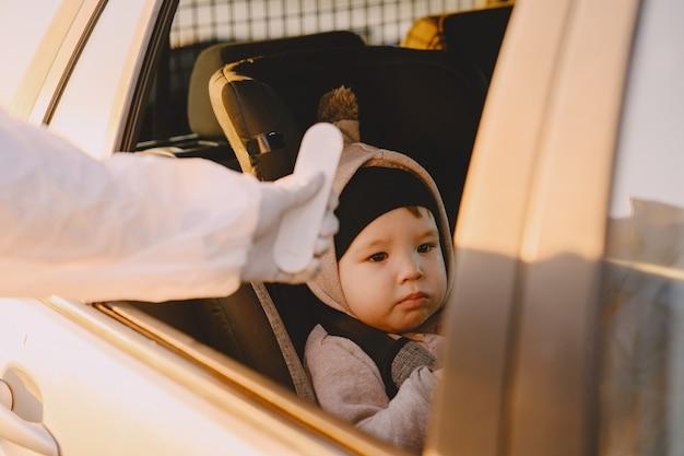 La persona in tuta protettiva controlla la temperatura Foto Gratuite