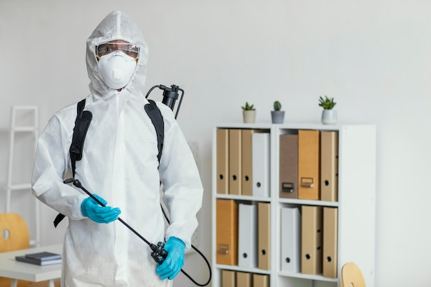 Person in protective suit getting ready to disinfect a room Free Photo