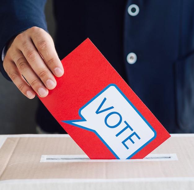 Лицо, положившее красный бюллетень в ящик для голосования Бесплатные Фотографии