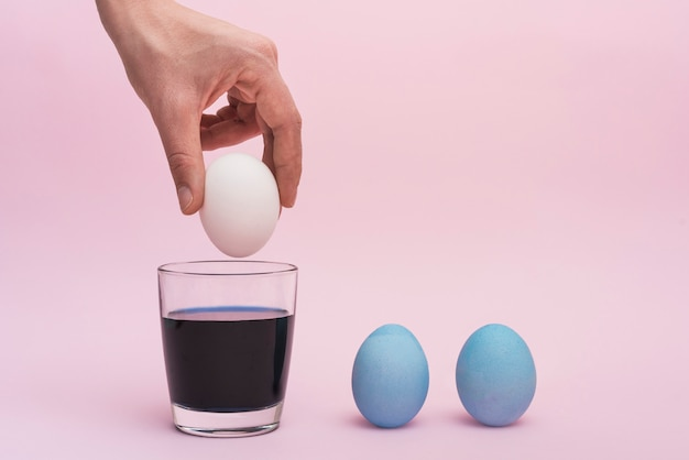 Person putting egg into glass with paint Free Photo