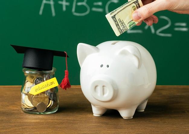 Человек кладет деньги в копилку с банкой и академической шапкой Premium Фотографии