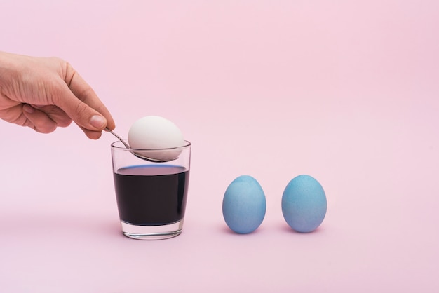Person putting spoon with egg into glass with paint Free Photo