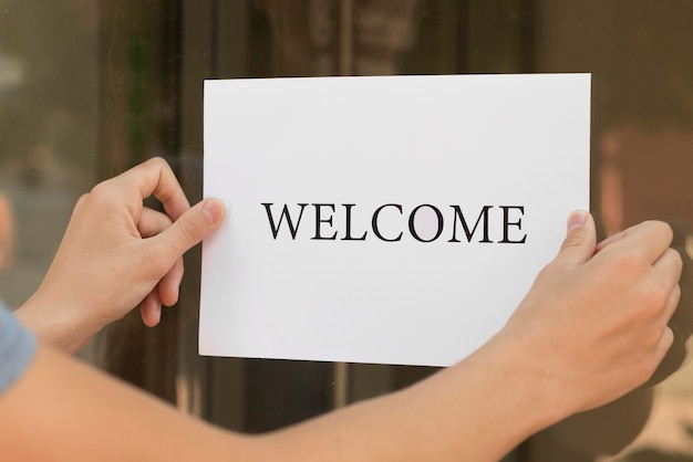 Person putting a welcome sign on a door Free Photo