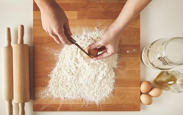 흰 밀가루 위에 닭고기 달걀을 깰 준비가 된 사람 무료 사진