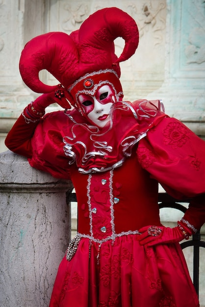 Person in red carnival costume of harlequin italian commedia dell arte  theatre Premium Photo