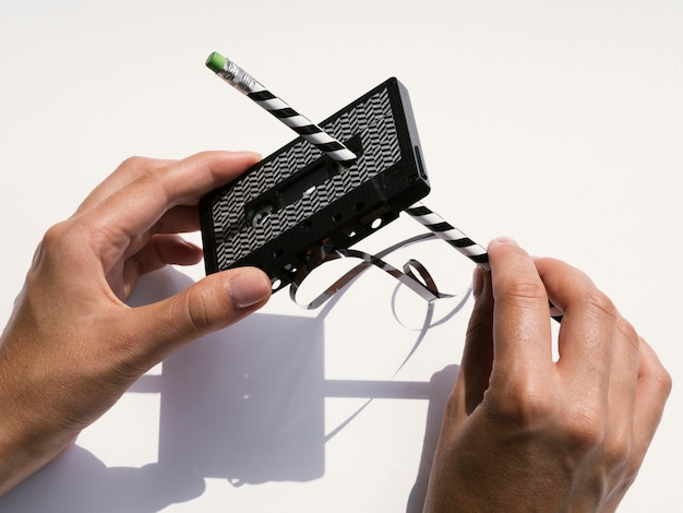 Person repairing black cassette tape with pencil Free Photo