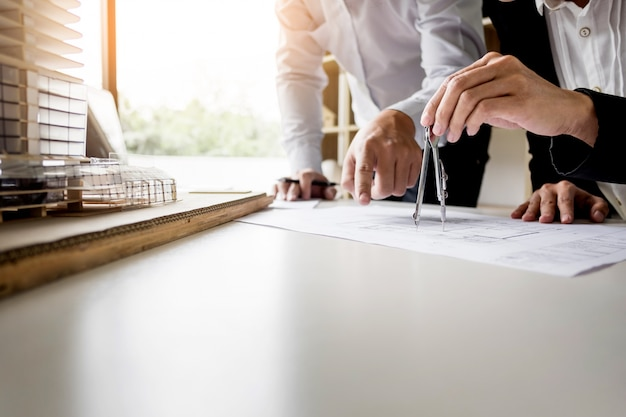 Person's engineer Hand Drawing Plan On Blue Print with architect equipment Premium Photo