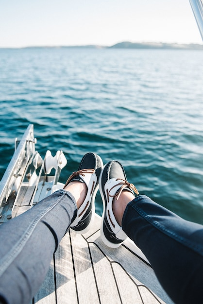 Person's feet on the boat sailing on the sea during daytime Free Photo