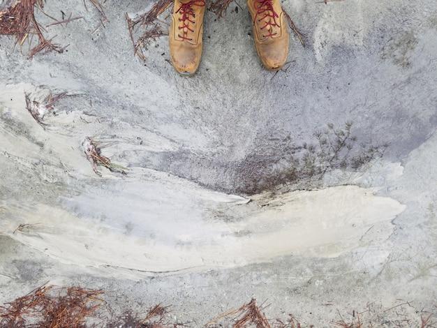 Ноги человека в коричневых кожаных туфлях, стоящих на выветрившейся бетонной земле Бесплатные Фотографии