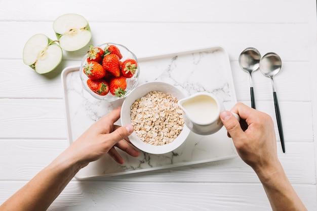 人の手は、テーブルの上の半分の青リンゴとイチゴのオート麦のボウルに牛乳を追加します。 Premium写真