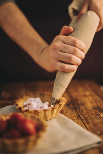 A person's hand filling the tart with pink whipped cream from icing bag on wooden table Free Photo