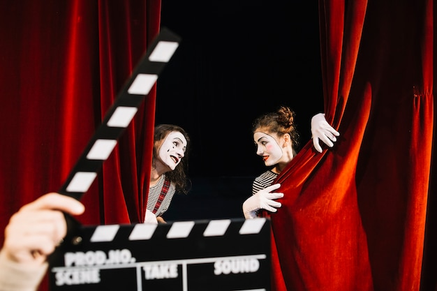 A person's hand holding clapperboard in front of two mime artist performing behind red curtain Free Photo