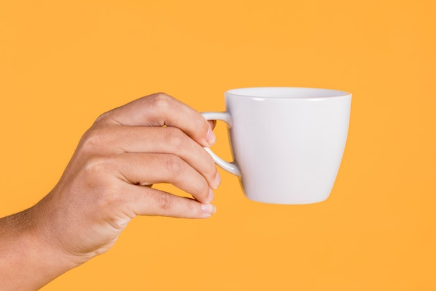 Person's hand holding coffee cup against colored background Free Photo