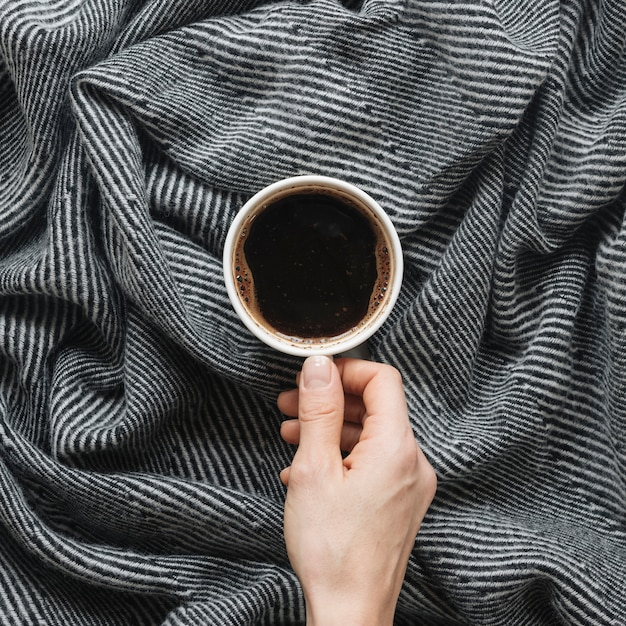 Person's hand holding coffee cup over cloth Free Photo