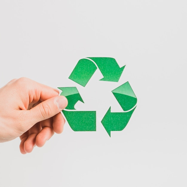 A person's hand holding green recycle symbol on white backdrop Free Photo