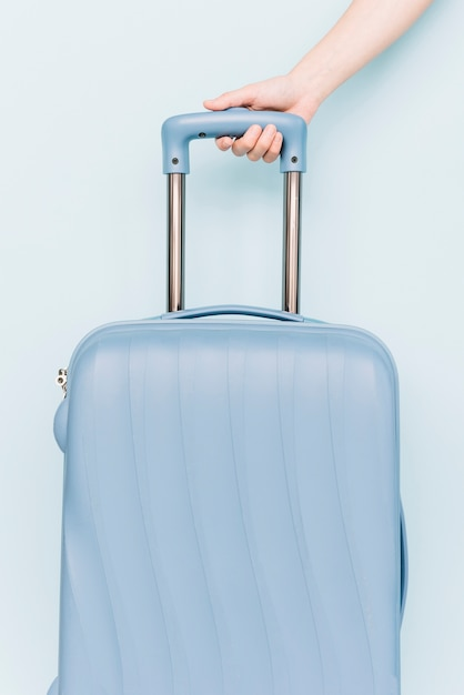 A person's hand holding handle of travel baggage against blue backdrop Free Photo