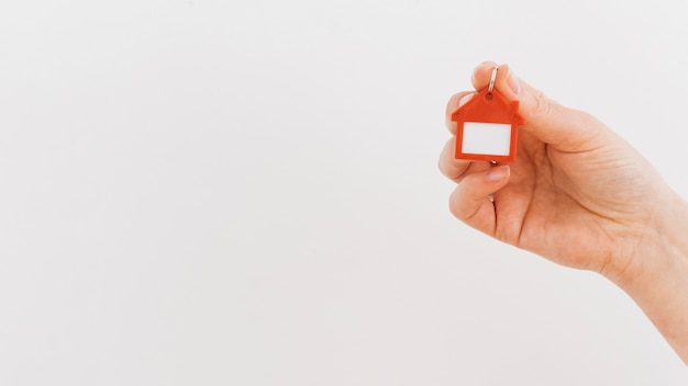 A person's hand holding house keychain on white backdrop Free Photo