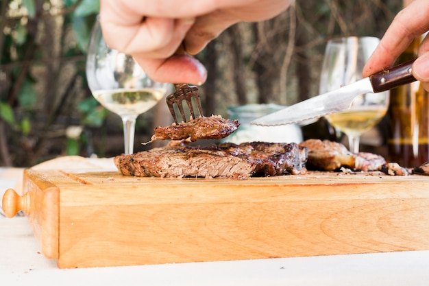 A person's hand holding knife and fork cutting grilled beef steak on chopping board Free Photo
