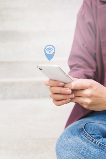 Person's hand holding mobile phone searching for wi-fi connection Free Photo