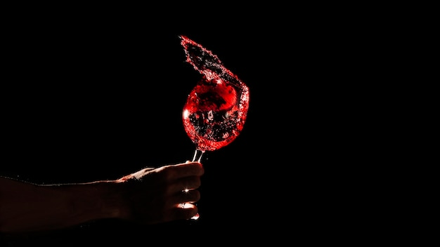 Person's hand holding red wine glass over black background Free Photo
