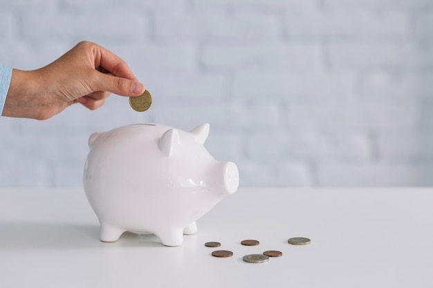 A person's hand inserting coin in white piggybank on desk Free Photo