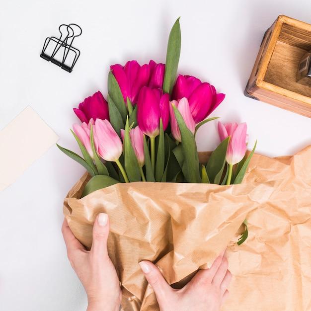 白い背景で隔離の上の茶色の紙とチューリップの花の花束を作る人の手 無料の写真