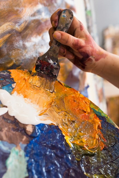 Person's hand painting with messy paint and paintbrush Free Photo