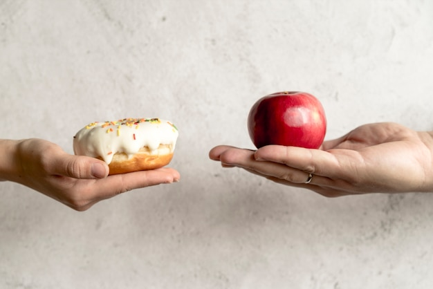 Person's hand showing donut and apple in front of concrete background Free Photo