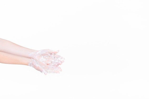 A person's hand in soapsuds over white background Free Photo