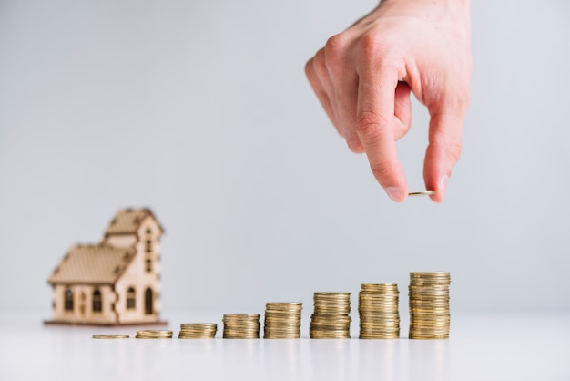 A person's hand stacking coins in front of house model Free Photo