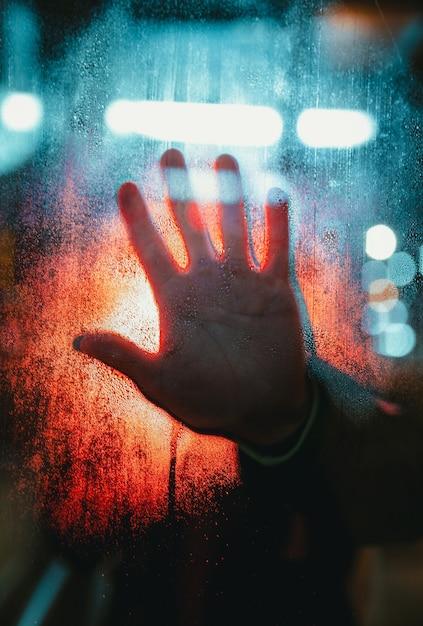 La mano della persona che tocca un vetro coperto di gocce di pioggia con luci bokeh Foto Gratuite