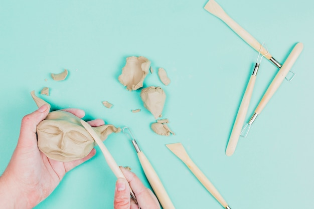 A person's hand using sculpting tools for making clay face on mint green backdrop Free Photo